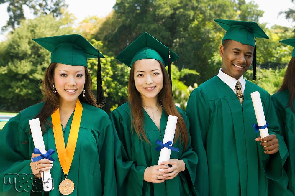Graduates hoisting diplomas outside university portrait