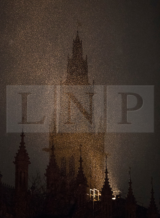 © Licensed to London News Pictures. 12/01/2017. London, UK. Snow flurries are illuminated by floodlights on the roof of Parliament. Rain and heavy snow are expected to hit most of the UK today. Photo credit: Peter Macdiarmid/LNP