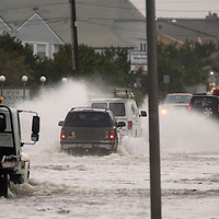(PPAGE1) Sea Bright 10/25/2005 A line of SUV's and trucks are the only vehicles able to navigate the flooded roads of Sea Bright as flood waters rose on Ocean Ave.  This was around the area just north of the Navesink Marina.   Michael J. Treola Staff Photographer....MJT