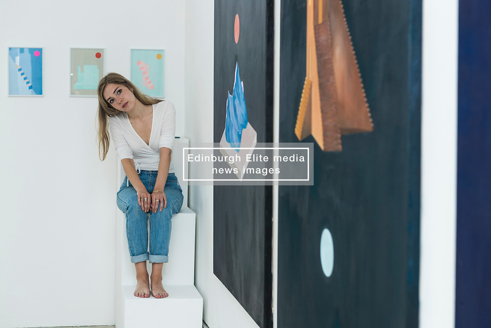 For nine days in June (1-9 June 2017), Edinburgh College of Art is transformed into vibrant gallery spaces exhibiting work from more than 500 graduating students at this year's Degree Show.<br /> <br /> For the first time, the former Fire Station on Lauriston Place – recently acquired by the University – will be used as part of Edinburgh College of Art's extensive exhibition. <br /> <br /> Work from 38 degree programmes will be on display – including architectural models, animated films, photography, textiles, jewellery and interior design.<br /> <br /> Sculpture student Michael Kay Terence's installations were inspired by the former Fire Station, where his work will be on show. The space features a bright turquoise Mini, which has been cut in half and crash-landed. <br /> <br /> Rachel McLellan has explored the themes of identity and tribalism by creating a giant web of brightly coloured T-shirts, emblazoned with slogans.<br /> <br /> Pictured: Joanna Wickham with a selection of her prints and paintings