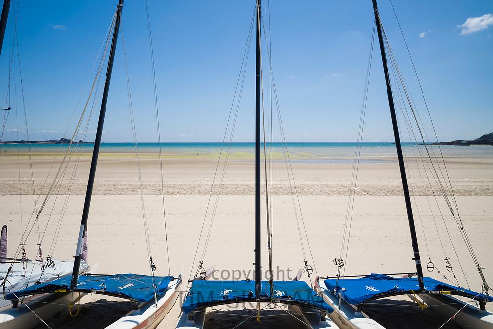 Row of catamarans on St Aubin's sandy beach, Jersey, Channel Isles