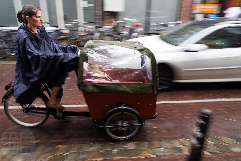 Een vrouw rijdt met een bakfiets met kinderen door de regen in Utrecht.<br /> <br /> A woman is cycling in the rain on a cargo bike with children in Utrecht.