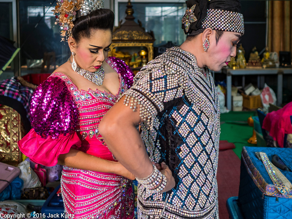 "30 JANUARY 2016 - NONTHABURI, NONTHABURI, THAILAND: A woman performer helps a male performer get into his costume before a ""likay"" show at Wat Bua Khwan in Nonthaburi, north of Bangkok. Likay is a form of popular folk theatre that includes exposition, singing and dancing in Thailand. It uses a combination of extravagant costumes and minimally equipped stages. Intentionally vague storylines means performances rely on actors' skills of improvisation. Like better the known Chinese Opera, which it resembles, Likay is performed mostly at temple fairs and privately sponsored events, especially in rural areas. Likay operas are televised and there is a market for bootleg likay videos and live performance of likay is becoming more rare.     PHOTO BY JACK KURTZ"