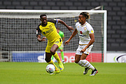 Burton Albion forward Lucas Akins and Milton Keynes Dons midfielder David Kasumu challenge for the ball during the EFL Sky Bet League 1 match between Milton Keynes Dons and Burton Albion at stadium:mk, Milton Keynes, England on 5 October 2019.