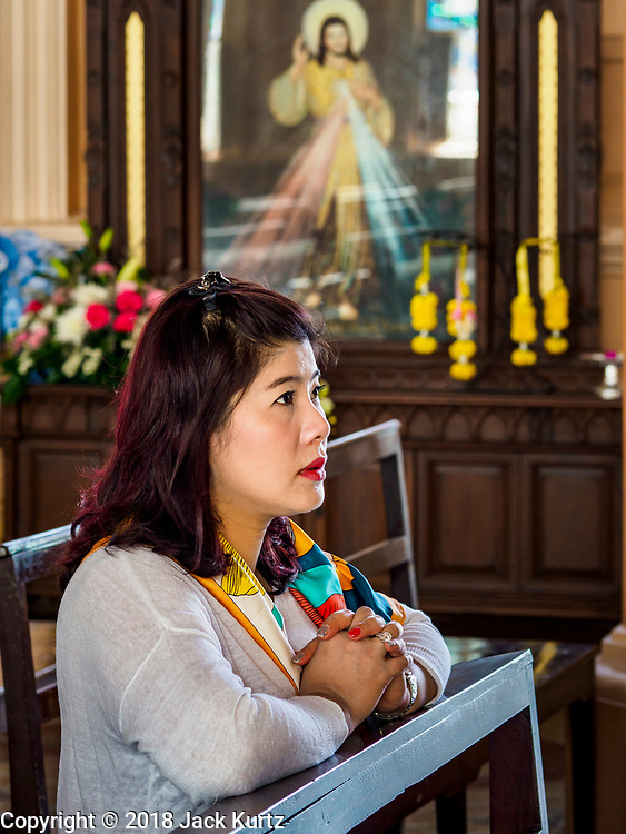 23 DECEMBER 2018 - CHANTABURI, THAILAND:  A woman prays in the Cathedral of the Immaculate Conception in Chantaburi. It is the largest Catholic church in Thailand and was founded more than 300 years ago by Vietnamese Catholics who emigrated to Thailand. The current cathedral building was sited and construction started while Chantaburi was occupied by French forces that had occupied neighboring Cambodia. The cathedral was finished after the French were expelled from Thailand. Chantaburi is the capital city of Chantaburi province on the Chantaburi River. Because of its relatively well preserved tradition architecture and internationally famous gem market, Chantaburi is a popular weekend destination for Thai tourists.   PHOTO BY JACK KURTZ