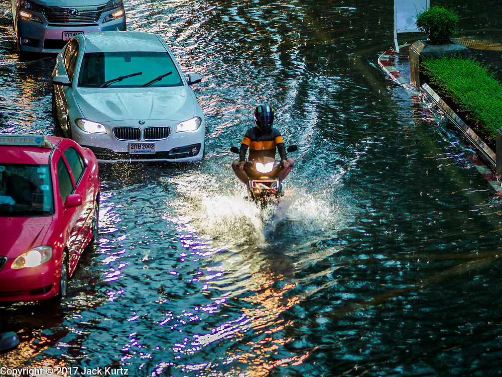 27 MAY 2017 - BANGKOK, THAILAND: A motorcycle cuts through traffic on Rama I Street, which was flooded by monsoonal rains. The rainy season in Bangkok usually starts in mid-June but started almost a month early this year. There have been daily thunderstorms and localized flooding throughout central Thailand since the middle of May.     PHOTO BY JACK KURTZ