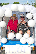 An elderly couple poses inside their cloud decorated golf cart during the annual Sullivan's Island Independence Day parade July 4, 2017 in Sullivan's Island, South Carolina. The tiny affluent sea island hosts a bicycle and golf cart parade through the historic village.