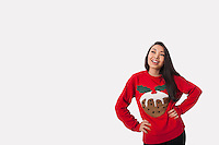Young woman in Christmas sweater standing with hands on hips over gray background