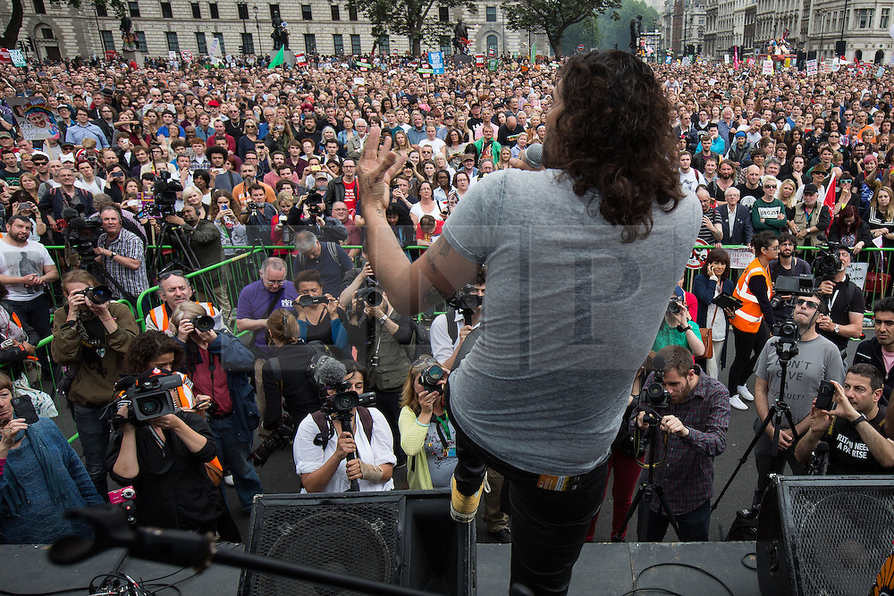 © Licensed to London News Pictures . 20/06/2015 . London , UK . RUSSELL BRAND speaking to the crowd in Parliament Square . Tens of thousands of people march from the Bank of England to Parliament , to protest economic austerity in Britain . Photo credit: Joel Goodman/LNP