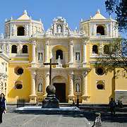 Plaza in front of the distinctive  and ornate yellow and white exterior of the Iglesia y Convento de Nuestra Senora de la Merced in downtown Antigua, Guatemala.