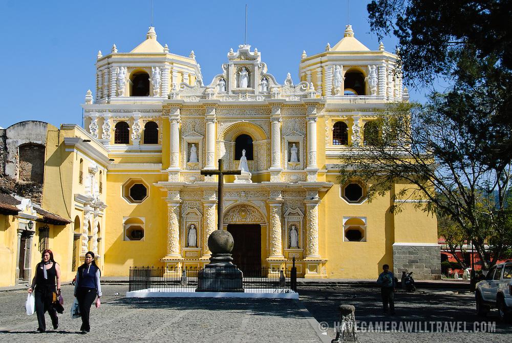Plaza in front of the distinctive  and ornate yellow and white exterior of the Iglesia y Convento de Nuestra Senora de la Merced in downtown Antigua, Guatemala.