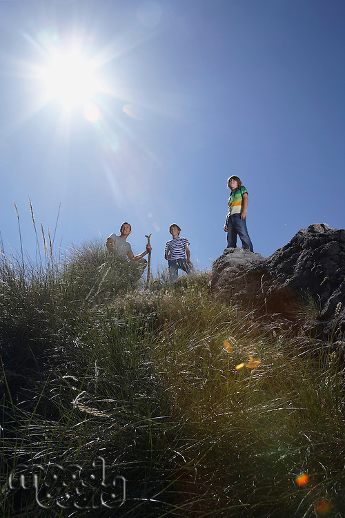 Father with two sons (7-9 10-12) on mountain top low angle view