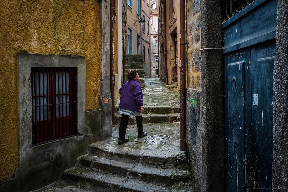 Woman walking at a narrow alley in Porto ribeira. Portugal