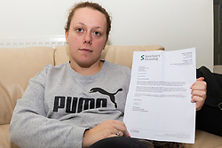 Dionne Burrows, 28, displays a letter from her Quayside House apartment block management, Sanctuary Housing, reminding residents that pest controllers will be arriving to fumigate the residential block following an infestation of false widow spiders. Dionne was bitten on the leg several weeks prior after which her GP prescribed antibiotics. Canning Town, London, October 30 2018.