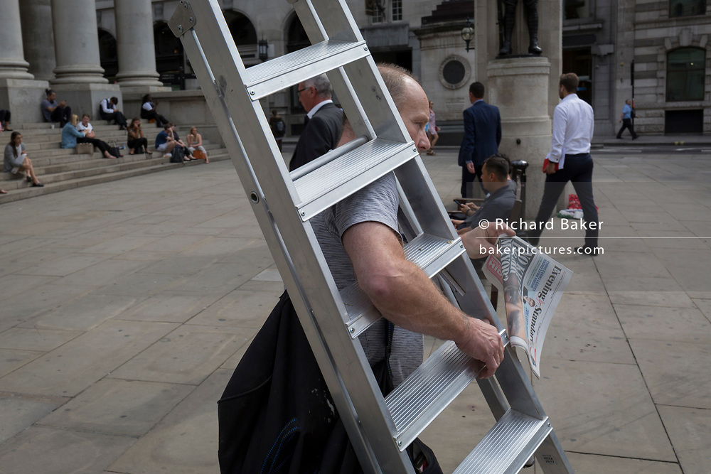 A workman carries lightweight aluminium stepladders and a copy of the Evening Standard, on 3rd September 2018, in London England.