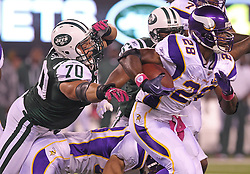 Oct 11, 2010; East Rutherford, NJ, USA; Minnesota Vikings running back Adrian Peterson (28) avoids a tackle by New York Jets defensive end Mike Devito (70) during the first half at the New Meadowlands Stadium.