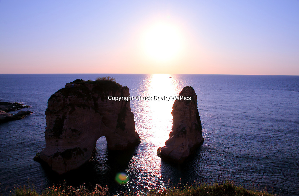 Beirut's Pigeon Rocks islands viewed from shore against the Mediterranean Sea's sunset.