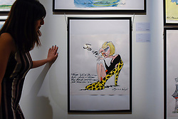 "© Licensed to London News Pictures. 31/03/2017. London, UK. A staff member views ""Sod Off"" by Gerald Scarfe (Est. GBP 2-3k), a caricature of Theresa May.  Press preview of ""Made in Britain"" at Sotheby's in New Bond Street.  The auction on 5 April celebrates innovative British art in the twentieth century as well as artwork by political cartoonist Gerald Scarfe. Photo credit : Stephen Chung/LNP"
