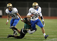 Wahlert's Brady Williams (80) is pulled down by Kennedy's David Hynek (52) during the first half of the game between Cedar Rapids Kennedy and Dubuque Wahlert at Kingston Stadium in Cedar Rapids on Friday night, October 21, 2011.