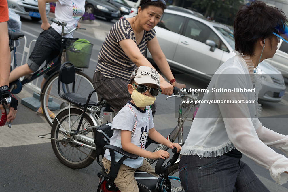 Child wearing mask, on back of a bicycle, in traffic in Beijing, China, Thursday 7th June 2012.