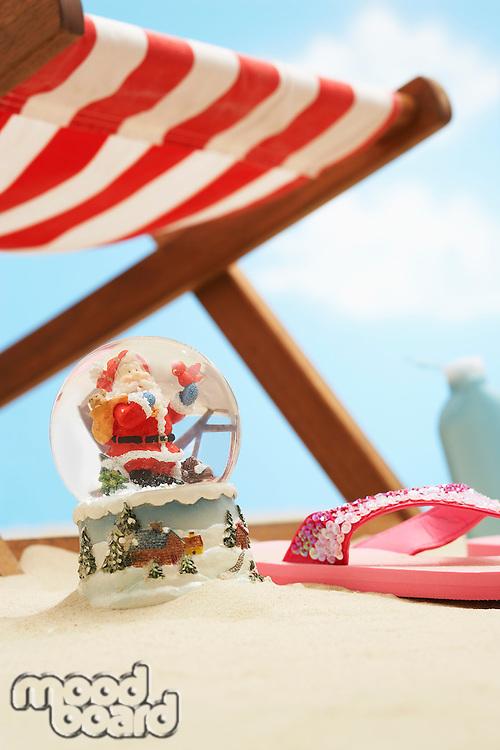 Souvenir santa snow globe under deckchair on beach close up