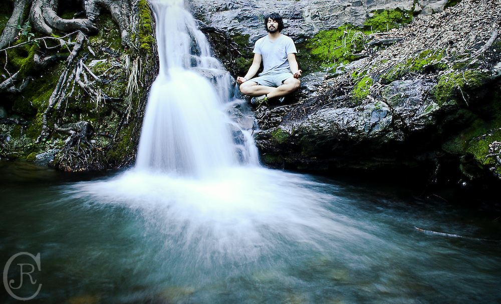 Joseph R Cisneros II meditates next to a waterfall in Rose Valley, California.