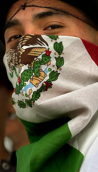 Aaron Hernandez, age 17, a student at Highland H.S. in Albuquerque wears a Mexican flag bandana over his face while attending an immigration rally in downtown Albuquerque, N.M., photographed Monday April 10, 2006.   (Ap Photo/The Albuquerque Journal, Pat Vasquez-Cunningham)