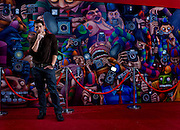 Marc Ecko photographed in the lobby of Ecko Enterprises, New York. The mural, designed by Ecko, puts visitors on the red carpet being photographed by paparazzi as they enter the front door.