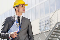 Young male architect with clipboard looking away outside office building
