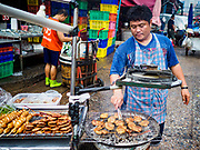 08 JUNE 2017 - BANGKOK, THAILAND:  A grilled meat vendor in Khlong Toey Market, Bangkok's main fresh market. Thai consumer confidence dropped for the first time in six months in May following a pair of bombings in Bangkok, low commodity prices paid to farmers and a sharp rise in the value of the Thai Baht versus the US Dollar and the EU Euro. The Baht is surging because of political uncertainty, related to Donald Trump, in the US and Europe. The Baht's rise is being blamed for a drop in Thai exports. This week the Baht has been trading at around 33.90 Baht to $1US, it's highest point in two years.     PHOTO BY JACK KURTZ