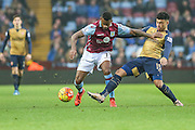 Aston Villa's Leandro Bacuna challenges with Arsenal's Alex Oxlade-Chamberlain for the ball during the Barclays Premier League match between Aston Villa and Arsenal at Villa Park, Birmingham, England on 13 December 2015. Photo by Shane Healey.