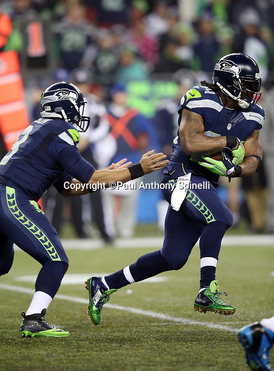 Seattle Seahawks running back Marshawn Lynch (24) takes a second quarter handoff from Seattle Seahawks quarterback Russell Wilson (3) and runs for a gain of 8 yards during the NFL week 19 NFC Divisional Playoff football game against the Carolina Panthers on Saturday, Jan. 10, 2015 in Seattle. The Seahawks won the game 31-17. ©Paul Anthony Spinelli