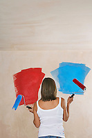 Woman facing wall painted on ble and red holding with paint rollers back view