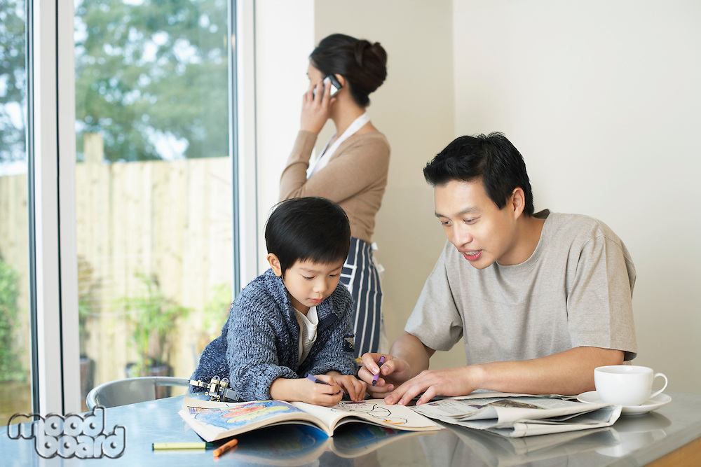 Father and Son coloring in Coloring Book on table mother talking on mobile