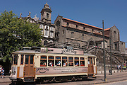 Traditional Portuguese tram passes beneath the Igreja De Sao Francisco (church) in Porto, Portugal.