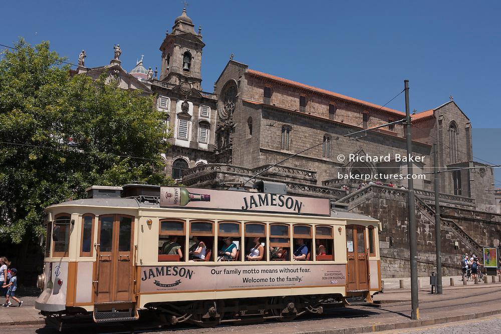 Traditional Portuguese tram passes beneath the Igreja De Sao Francisco (church) in Porto, Portugal.
