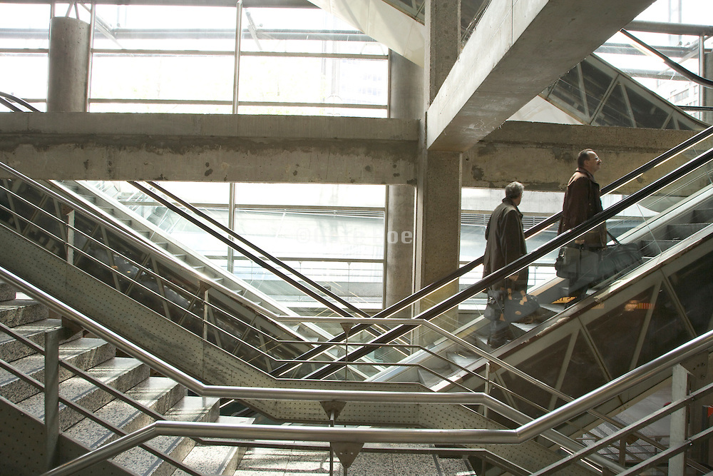 two businessmen going up stairs in a station