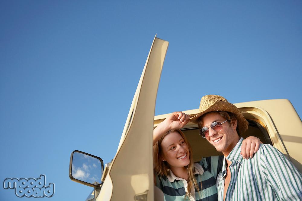 Young couple standing in doorway to van head and shoulders