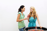 Two young women drinking cocktails by roulette wheel