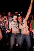YOUNG COOL COUPLE IN CLUB DANCING AND CHEERING WITH ARMS PUNCHING THE AIR