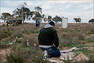 La vie quotidienne dans le camp Choucha à 8km de la frontière Libyenne. Un homme prie, un autre est aux toilettes. Plus de 140 000 réfugiés ont déjà quitté la Libye par la Tunisie ou l'Egypte et des milliers continuent d'arriver chaque jours. Jeudi 24 Février 2011, camp Choucha, Tunisie..© Benjamin Girette/IP3 press
