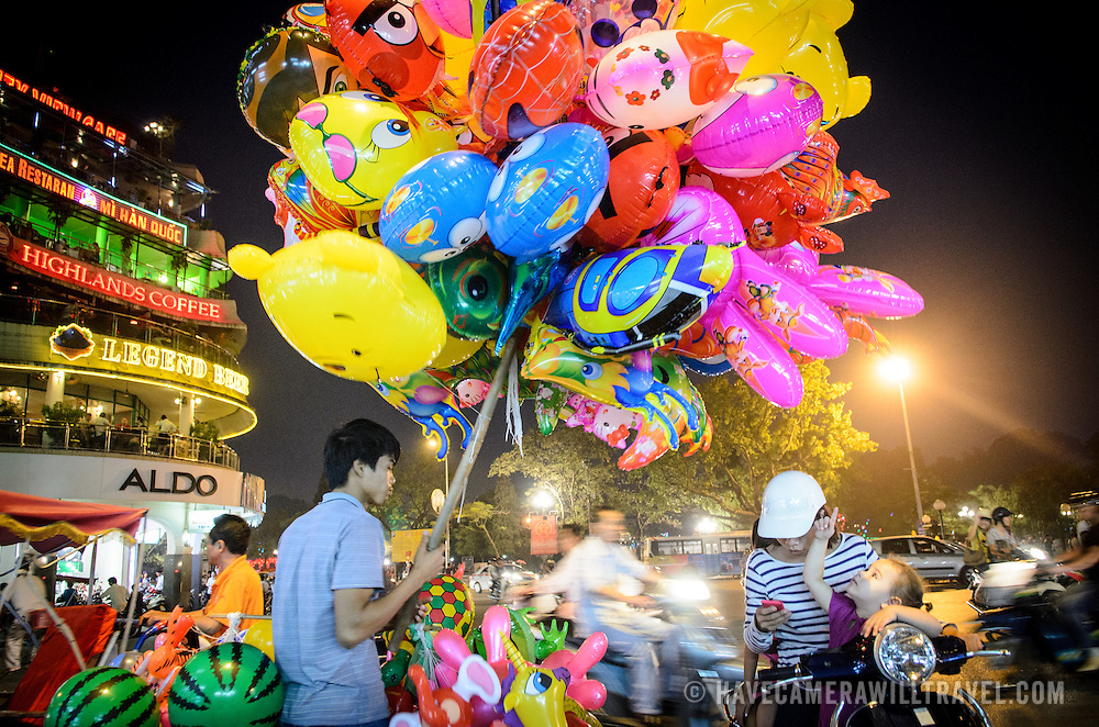 A man sells colorful helium balloons at a busy intersection in Hanoi's Old Quarter.