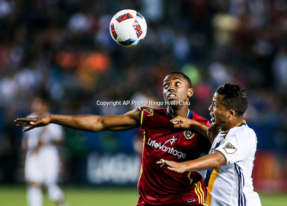 Real Salt Lake defender Aaron Maund, left, and Los Angeles Galaxy forward Giovani dos Santos battle for a ball in the first half of an MLS soccer game in Carson, Calif., Saturday, April 23, 2016. (AP Photo/Ringo H.W. Chiu)