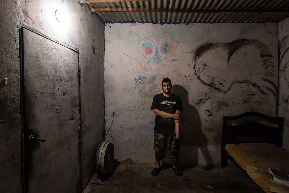 MARACAY, VENEZUELA - JULY 4, 2016: Schizophrenic patient, Accel Simeone poses for a portrait among the dozens of original hip hop songs that he has written on the walls of his bedroom. The economic crisis that has left Venezuela with little hard currency has already hit its health system, leaving hospitals without antibiotics, surgeons without gloves and patients dying on emergency room tables.  But beyond the hospital wards, thousands more mental health patients—many of whom had been living relatively normal lives at home with their families under medication—are slipping back into relapse for lack of basic psychiatric medications which control their symptoms, medical experts say. Accel  hears voices that urge him to commit violent acts. After three weeks without olanzapine, a drug used to control his paranoia, the voices inside Accel's head ordered him to kill his brother Gerardo.  When he refused, they ordered him to cut off his arm, and so he attacked himself. He took an electric circular saw from the family's garage, switched it on and began slicing into his arm. Soon his father found him and wrested the tool from his son's bloody hands. PHOTO: Meridith Kohut for The New York Times
