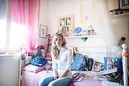 Firenze, Italia - 6 giugno 2013. Flavia Fondelli, sorella gemella di Carlotta (morta a causa di un incidente stradale), ritratta (sul letto della gemella ricoperto di oggetti che le appartenevano) nella stanza che condivideva con Carlotta all'interno sua abitazione a Firenze. Sulle pareti della stanza, e del resto di casa, sono affisse fotografie di Carlotta. Flavia e Carlotta condividevano tutto delle loro vite.<br /> Ph. Roberto Salomone<br /> ITALY - A portrayt of Flavia Fondelli (in the picture on the bed of her sister full of objects that she owned), twin sister of Carlotta, who died after a car accident. The walls of the bedroom, as the walls of the other rooms of her house in Florence are full of pictures of Carlotta.