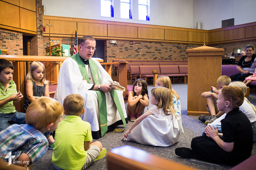 The Rev. Jonathan Huehn, associate pastor, leads a children's message Sunday, July 27, 2014, during worship at Christ Lutheran Church in Normal, Ill. LCMS Communications/Erik M. Lunsford