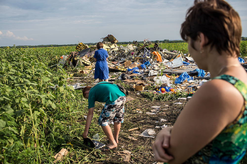 RASSIPNOYE, UKRAINE - JULY 19: People look at debris from Malaysia Airlines flight MH 17 which landed in a field of sunflowers on July 19, 2014 in Rassipnoye, Ukraine. Malaysia Airlines flight MH17 was travelling from Amsterdam to Kuala Lumpur when it crashed killing all 298 on board including 80 children. The aircraft was allegedly shot down by a missile and investigations continue over the perpetrators of the attack. (Photo by Brendan Hoffman/Getty Images) *** Local Caption ***