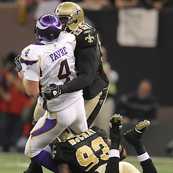 Jan 24, 2010; New Orleans, LA, USA; Minnesota Vikings quarterback Brett Favre (4) is hit by New Orleans Saints defensive tackle Remi Ayodele (92) and defensive end Bobby McCray (93) during the second half of the 2010 NFC Championship game at the Louisiana Superdome. Mandatory Credit: Derick E. Hingle