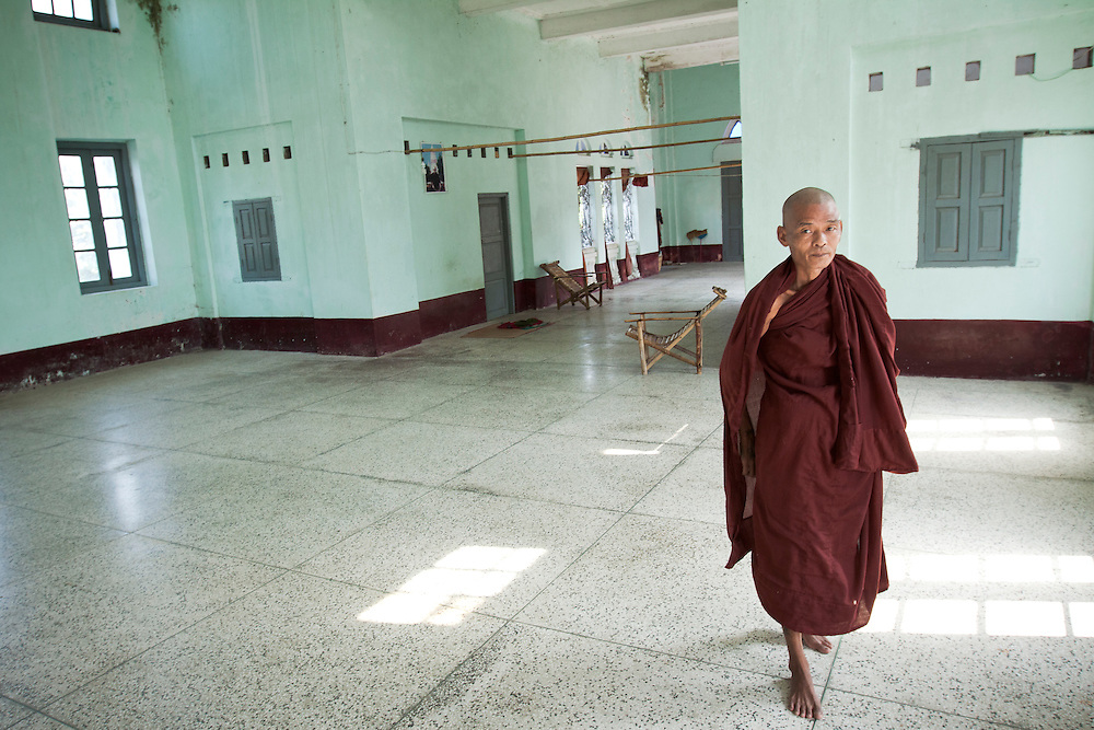 Buddhist monk guides visitors in small monastery near Yangon in Myanmar.