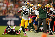 Oct 14, 2012; Houston, TX, USA; Green Bay Packers wide receiver James Jones (89) runs down the sideline after breaking a tackle by Houston Texans cornerback Kareem Jackson (25) during the first quarter at Reliant Stadium. Mandatory Credit: Thomas Campbell-thomasgcampbell.com